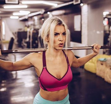 Determined blonde female athlete having a weight training in a health club